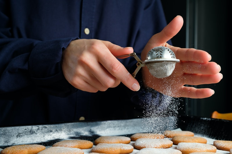 A person sifts sugar over cookies. Baking with Tourette Syndrome TikTok videos raise awareness about what it's like to live with tics.