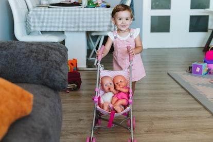 toddler pushing baby dolls in stroller