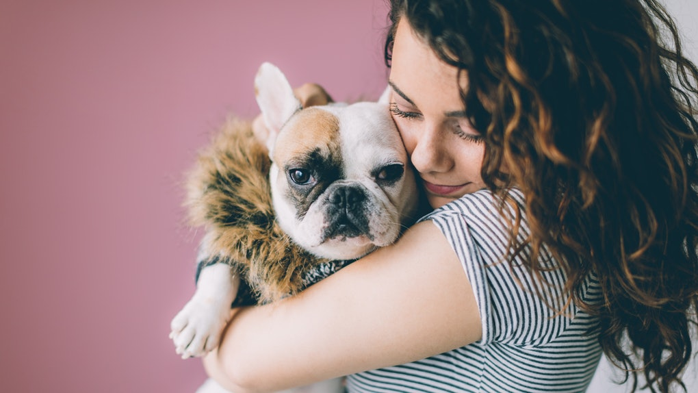 A woman holds her dog in front of a pink wall for Valentine's Day.