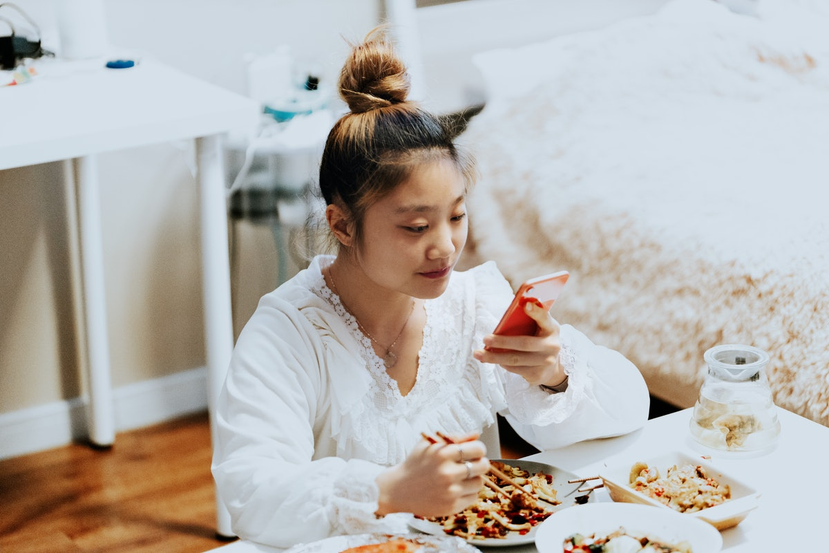 A young woman eats take out food in her bedroom, while posting an Instagram picture on her phone.