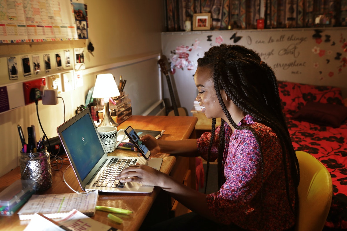A young woman plays on her phone, while sitting at her desk in a decorated bedroom.