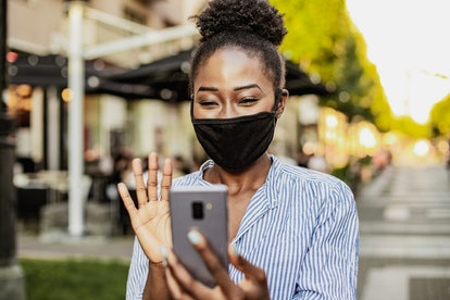 A woman in a mask waves hi to a person she recognizes via facetime.