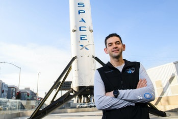 Jared Isaacman standing in front of a SpaceX rocket.