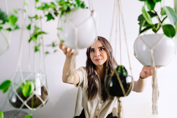 A young woman holds macrame plant hangings from TikTok.