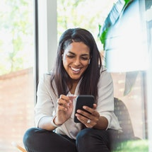 A young Black women laughing at a phone, sending a funny text to ask someone out.