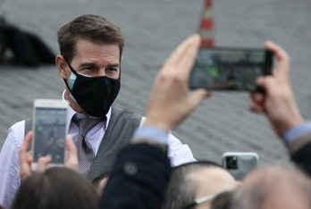 Tom Cruise wearing a face mask in front of fans, who are holding up two smartphones as cameras.