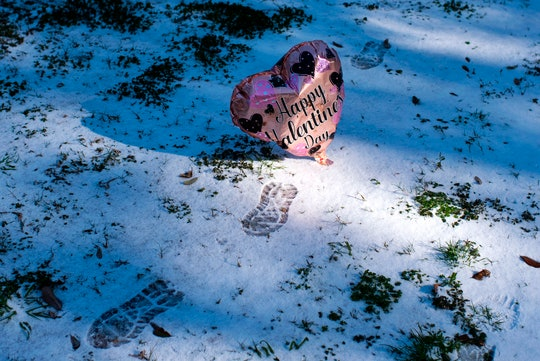 A deflating Valentine's Day balloon rests in the snow in Texas during a severe winter storm that has brought widespread power outages and a rise in carbon monoxide poisoning cases to the state.