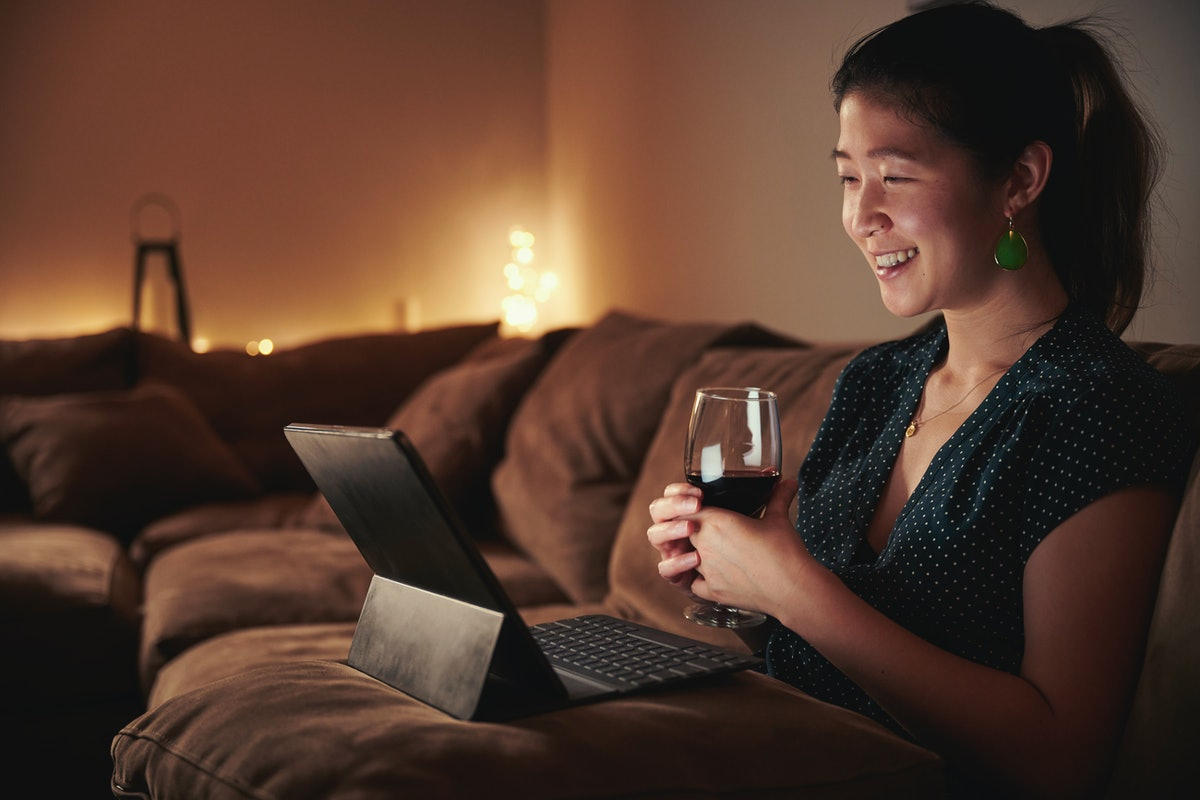 A woman enjoys a glass of wine while sitting on her couch with her tablet in her lap.