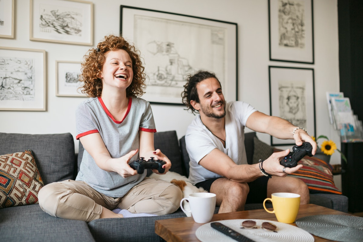 A young couple plays video games and laughs while sitting on their couch.