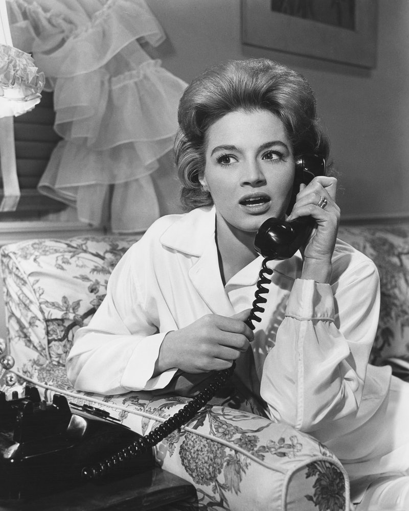A woman with a shocked expression on a corded phone. The LOLA cup text hotline will answer questions about menstrual cups.