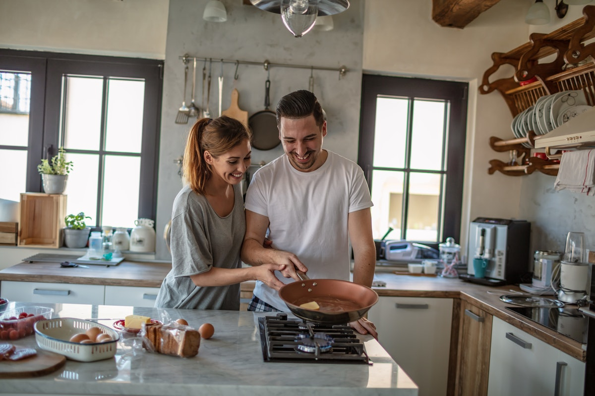 A happy couple fries an egg to make egg sandwiches in their bright kitchen.