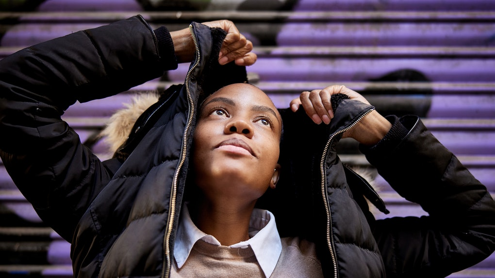 A young woman pulls a black puffer jacket over her head, while posing in front of a purple wall.