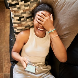 A woman on her couch at home cringes at her Instagram search history. Here's how to clear your Instagram search history and Instagram search suggestions.