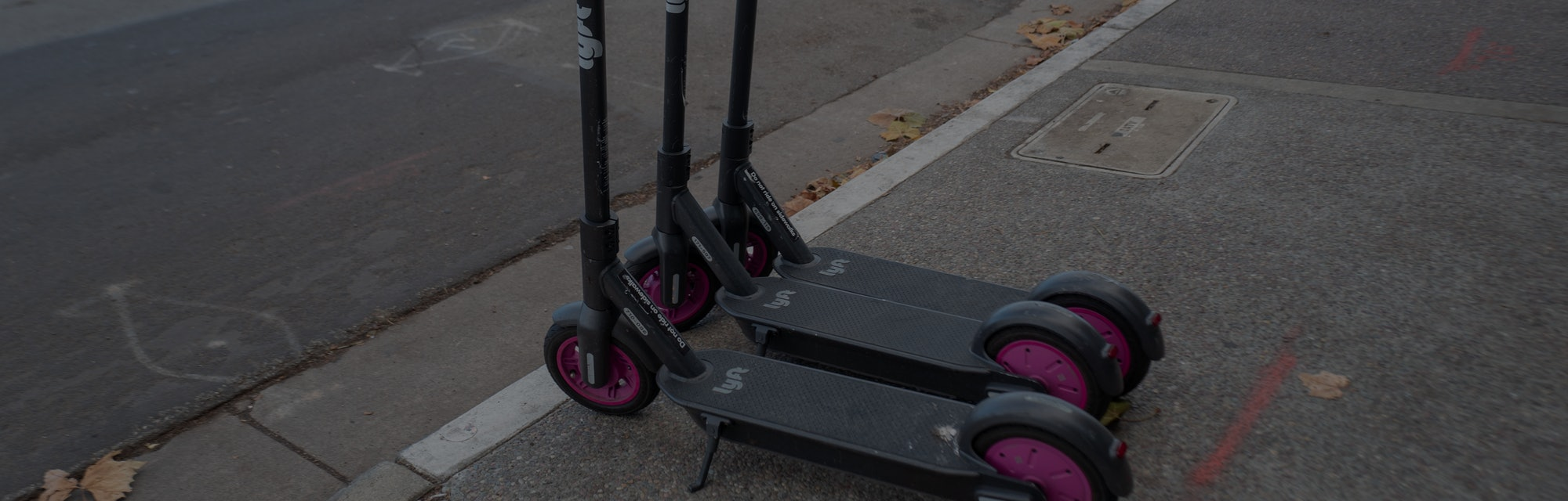 Two Lyft electric scooters parked on a sidewalk.