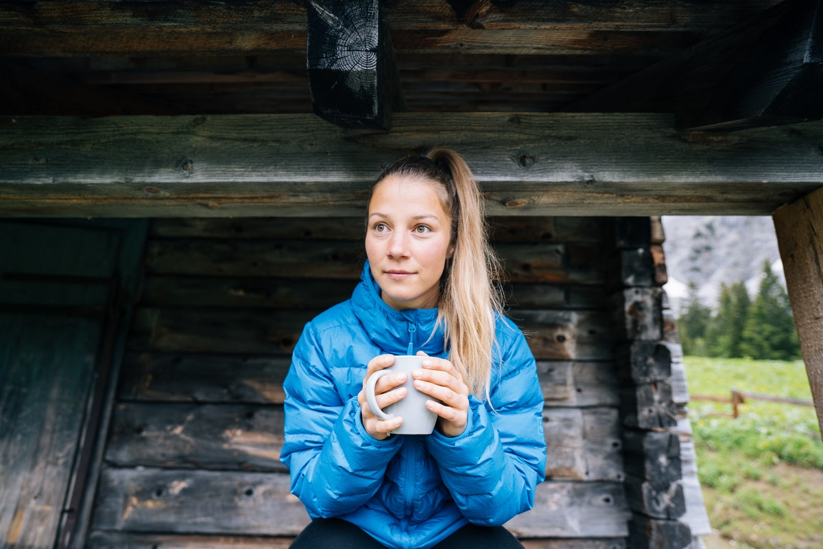 A young woman enjoys a hot cup of tea while wearing a bright blue puffer jacket in the outdoors.