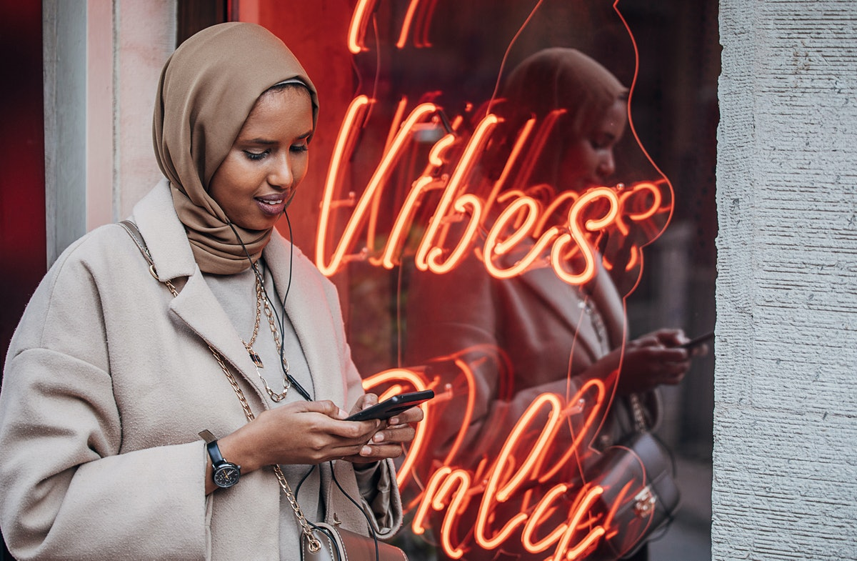 A woman wearing hijab checks her messaging apps in front of a neon sign.
