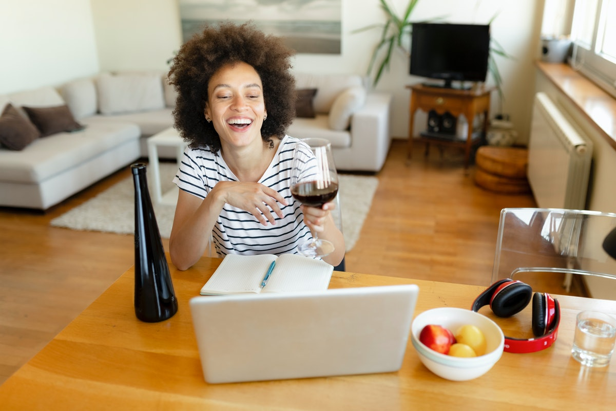 A happy woman laughs while enjoying a glass of red wine and taking a virtual wine tasting class for Galentine's Day.