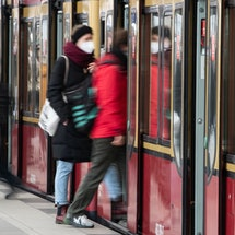 A person wears a mask while boarding a train. You might be able to travel safely after getting your COVID vaccine, but you still need to take community safety precautions.