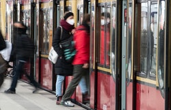 A person wears a mask while boarding a train. You might be able to travel safely after getting your ...