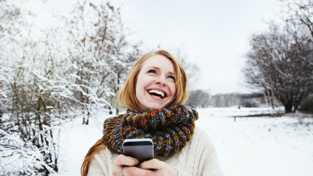 A happy woman laughs while typing on her phone and standing outside in the snow.