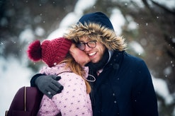 woman giving man a kiss in winter on hike