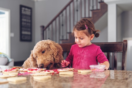 little girl and dog making valentine's day cookies