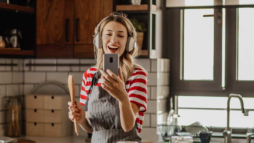 A woman in her kitchen looks at her phone while following a Super Bowl snack TikTok recipe.