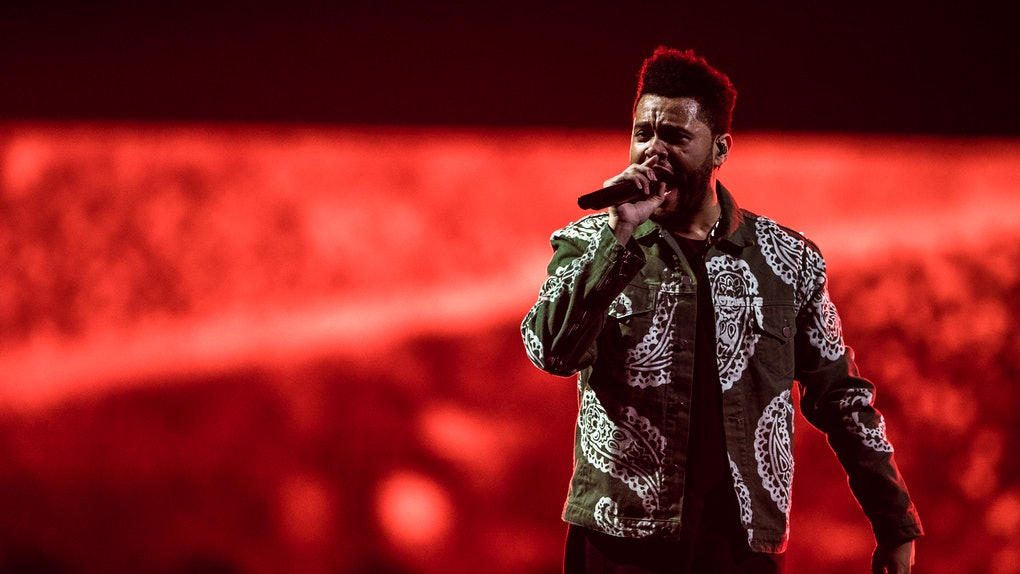 The Weeknd sings on stage in front of a glowing red backdrop.