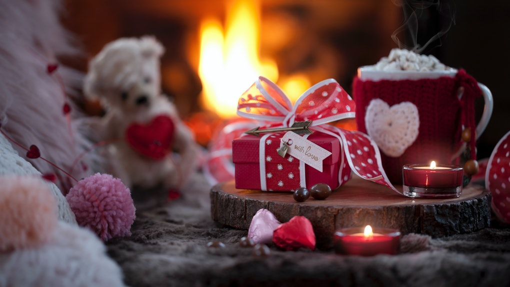 A Valentine's Day spread of hot cocoa and chocolates is placed next to a fireplace.