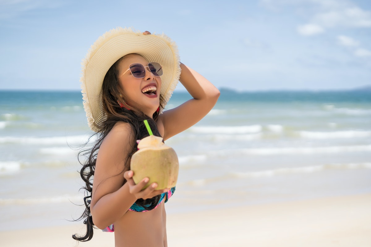 A happy woman with a coconut drink walks on the beach with her sunhat on spring break.