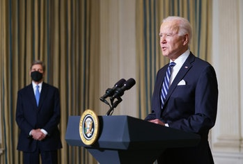 President Biden speaking at a lectern with climate envoy John Kerry in the background.