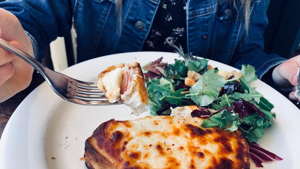 A woman enjoys a cheesy bread dish.