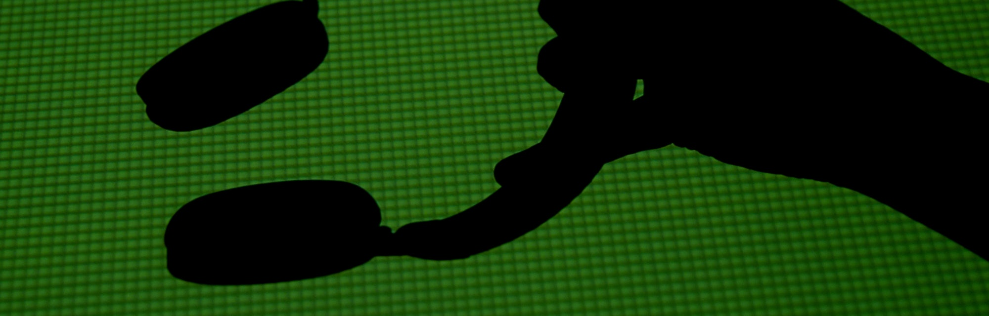 Silhouette of a hand holding a pair of headphones.