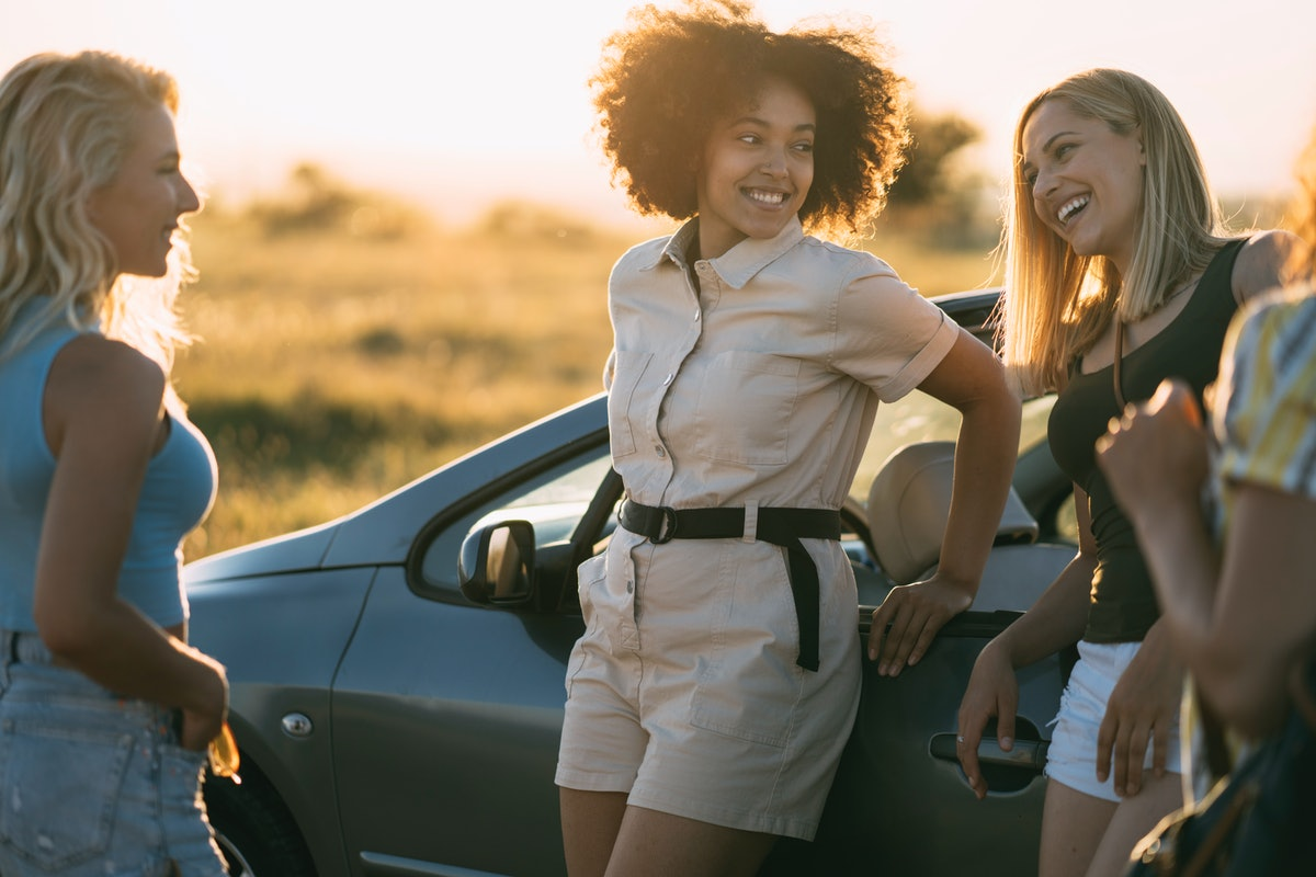 A group of friends hang out next to their car, talking while on a road trip.