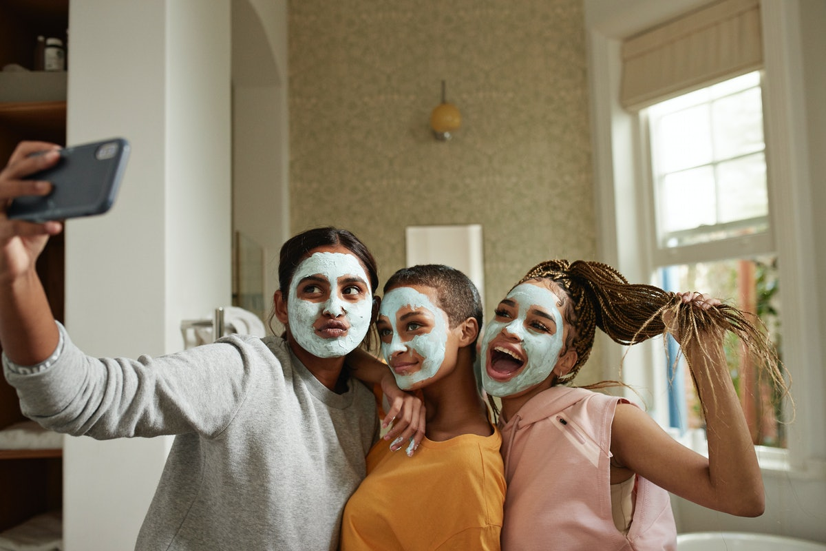 A group of young women take a selfie while doing facials at home during spring break.