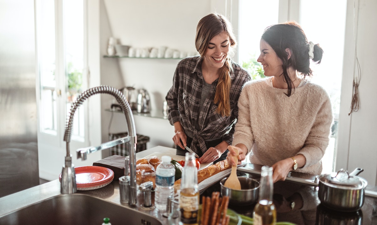 Two young women smile while cooking in their kitchen on spring break.