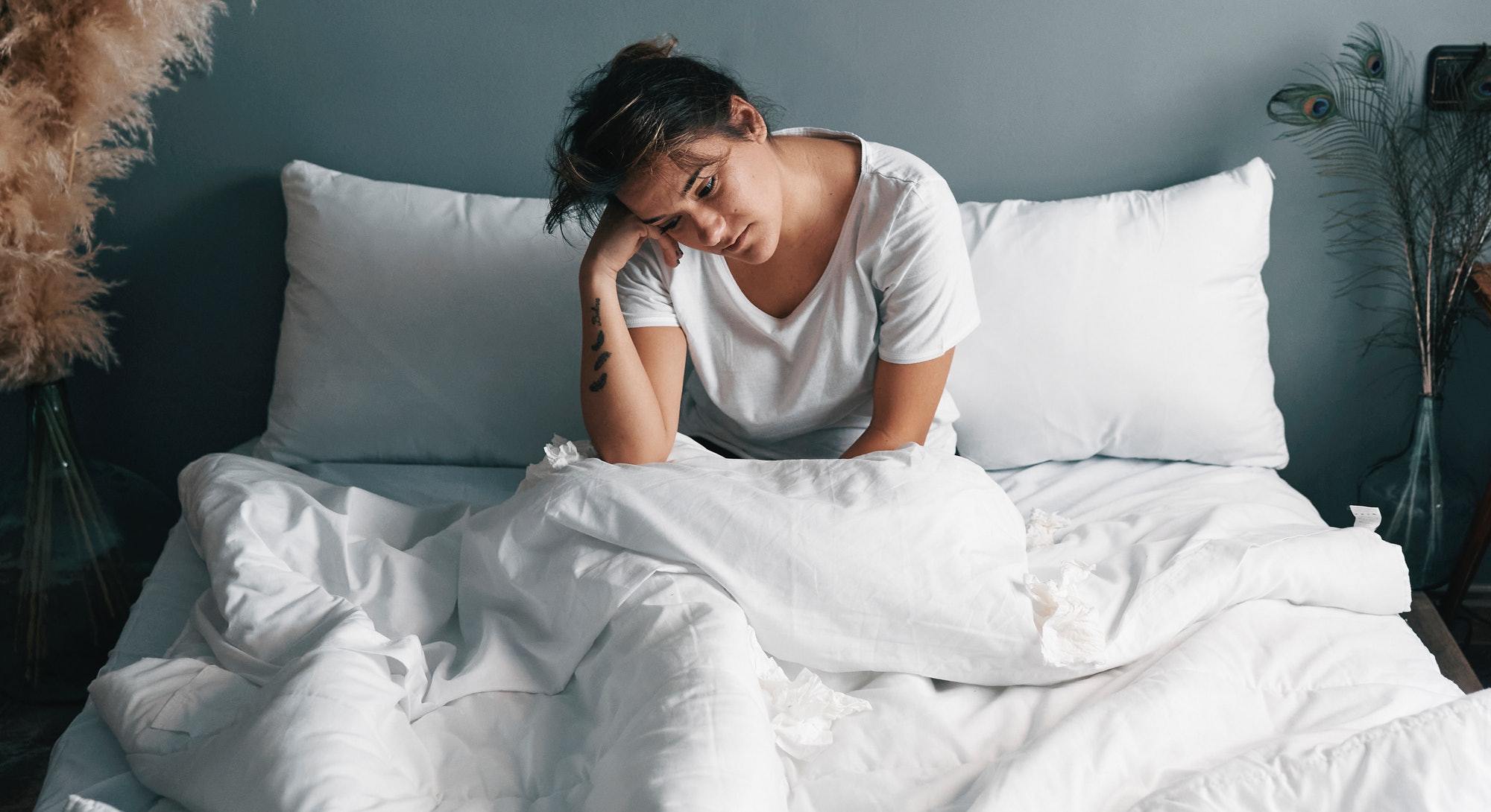 A woman lies in bed next to pampas grass, experiencing fatigue after a mild covid case turned into longhaul symptoms 6 months later.
