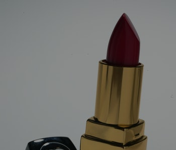 A lipstick by Chanel is seen on the screen. The color of the lipstick is deep red. The container is black and gold.