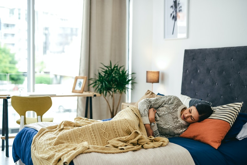 A person lies down in their bed, slightly curled up and holding their stomach. COVID can feel like f...
