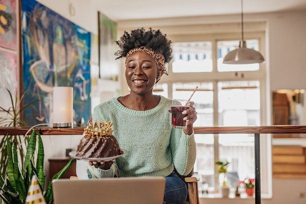 A happy woman holds up a birthday cake and cocktail while on a virtual birthday celebration call.
