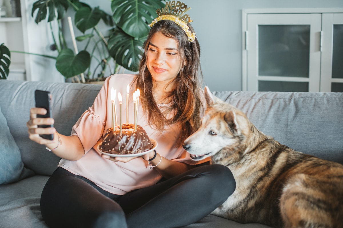 A happy woman holds a birthday cake and poses on the couch with her dog for a selfie.