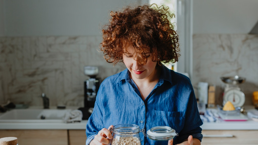 A woman looks into a jar of oats in her kitchen.