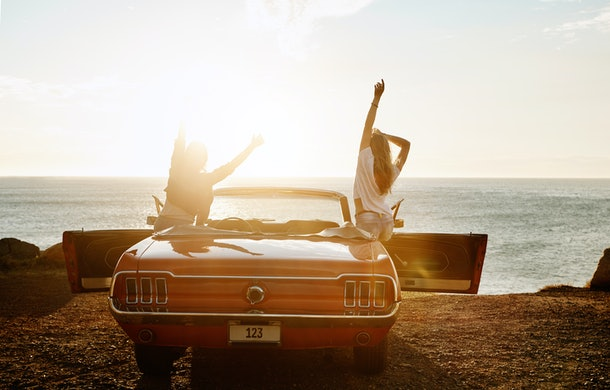 Two girls pose in a red classic mustang by the beach on a road trip.