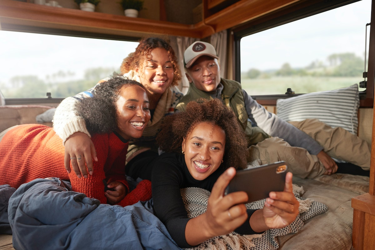 A group of friends all huddle close together for a picture together in the back of their RV.