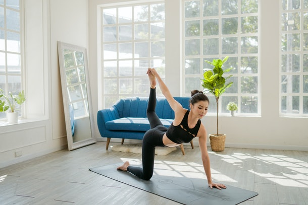 A brunette woman strikes a yoga pose on a mat in her bright home while doing a virtual yoga class.