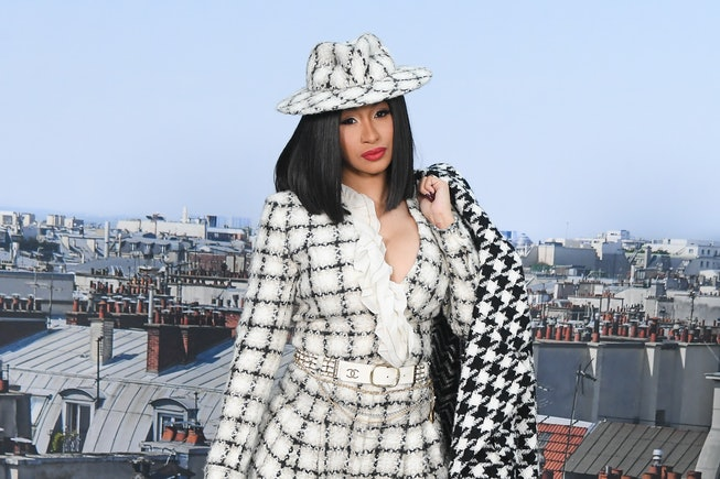 Cardi B, wearing a white jacket and matching hat