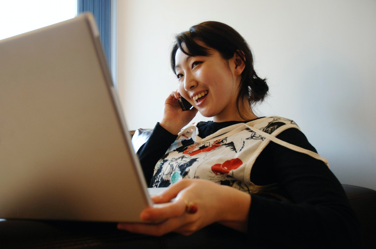 A young woman talks on the phone while holding her laptop.
