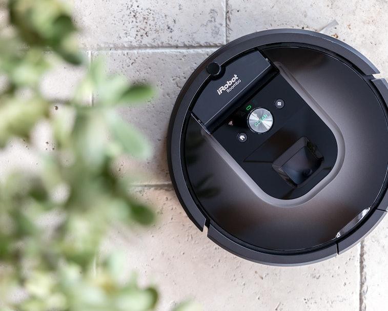 An iRobot Roomba is seen placed near a bush.