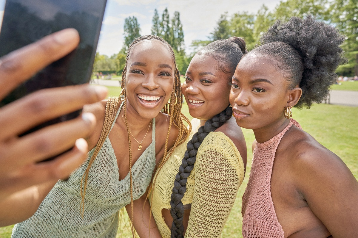 Three sister pose for a picture together on their phone while outside.