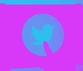 Twitter's logo is seen on a screen in a dark setting. A finger is pointing at the signature bird.